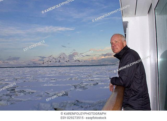 Passenger on deck of cruise ship traveling through ice field in Antarctica