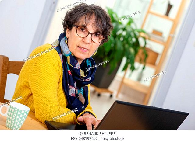 a portrait of beautiful brunette mature woman with a laptop at home