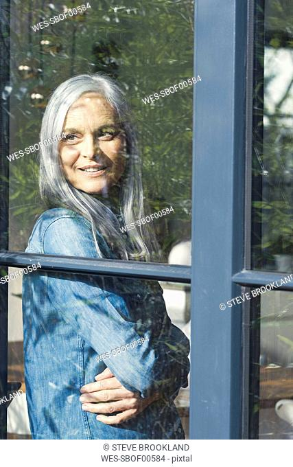 Senior woman looking out of window, smiling
