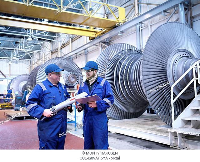 Engineers discussing rotor blade in turbine repair workshop