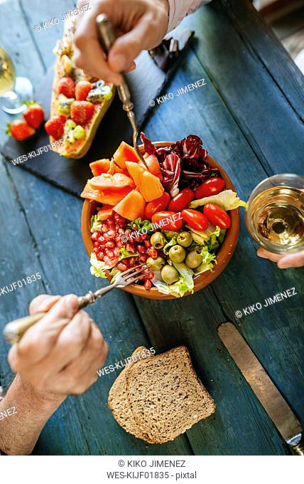 Close-up of woman's hands eating salad of tomato, pomegranate, papaya and olives
