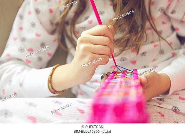 Caucasian girl knitting with rainbow loom