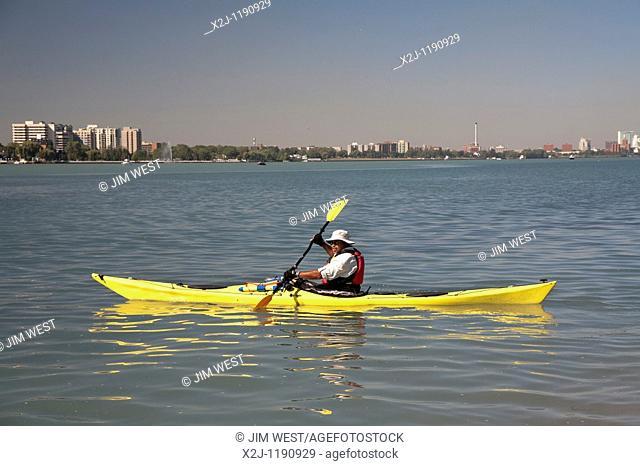 Detroit, Michigan - A man paddles a wooden kayak in the Detroit River