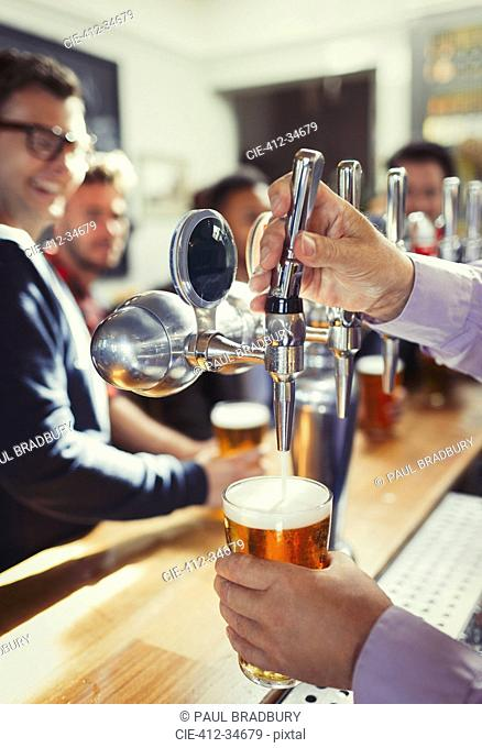 Close up bartender pouring beer from tap handle behind bar