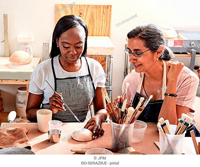 Women painting pottery in workshop