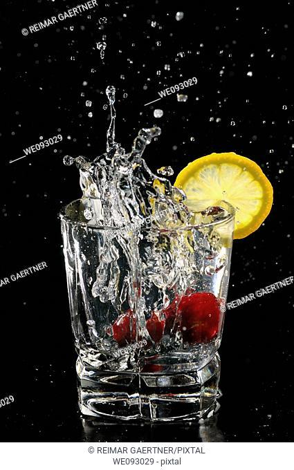 Cherries splashing into sparkling water glass with lemon slice on black background