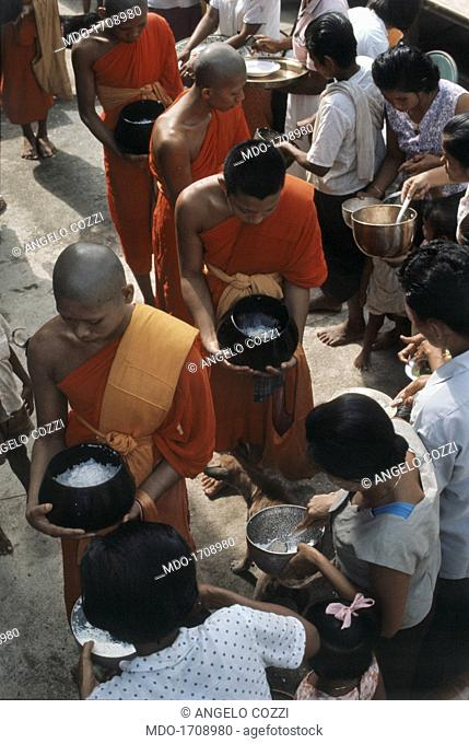 Some Buddhist monks receive offerings from population . Some Buddhist monks receive food offerings from the population. Buddhist monks arrive in the city in the...