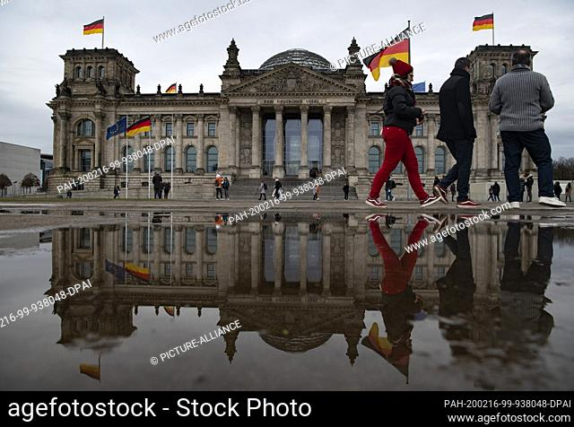 16 February 2020, Berlin: The Reichstag, where German flags are waving, is reflected in a puddle of rain on this rainy and windy Sunday