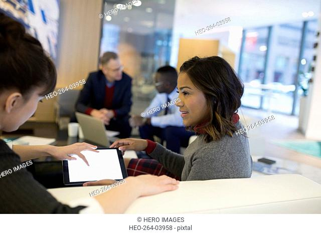Young businesswomen using digital tablet in office lobby