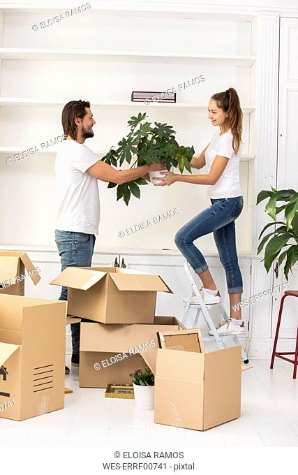 Couple unpacking cardboard boxes and furnishing new home