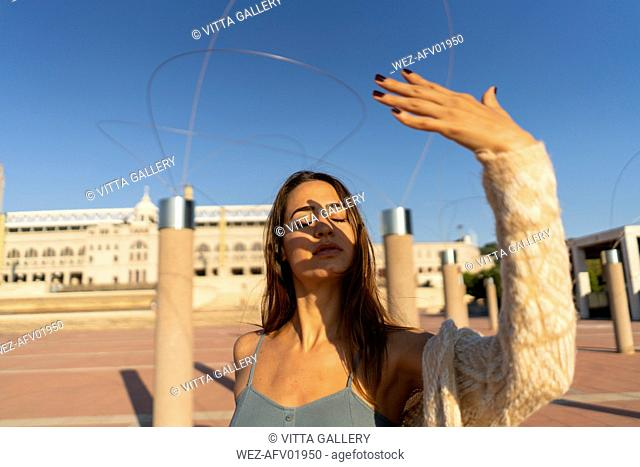 Spain, Barcelona, Montjuic, young woman raising her hand in sunlight