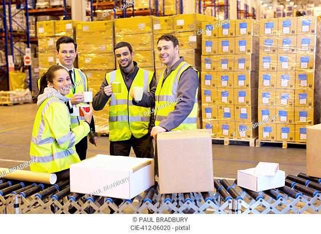 Workers drinking coffee in warehouse