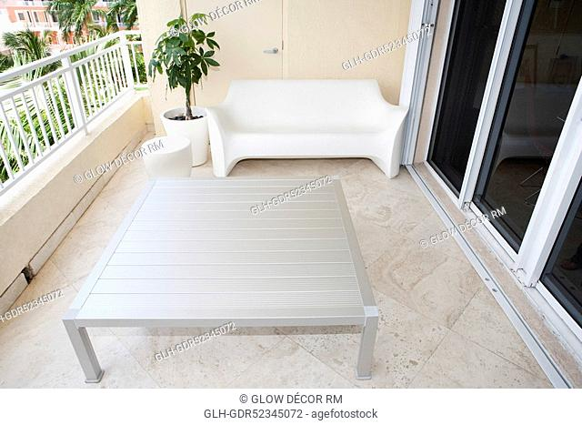 Couch and potted plant in the balcony of a house