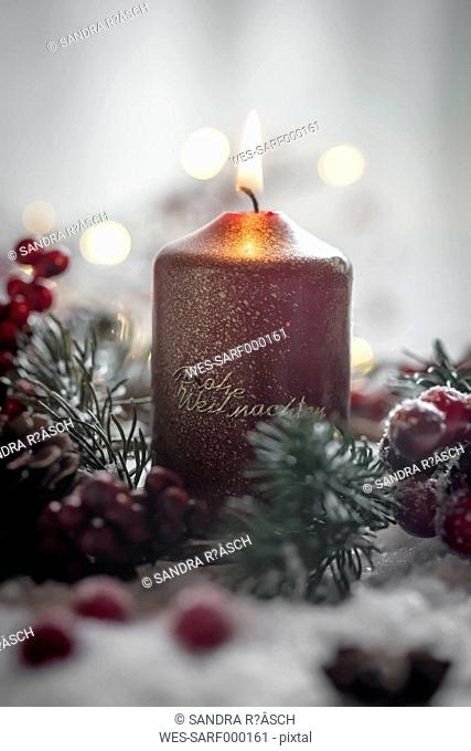 Lighted Christmas candle, fir branch and artificial snow