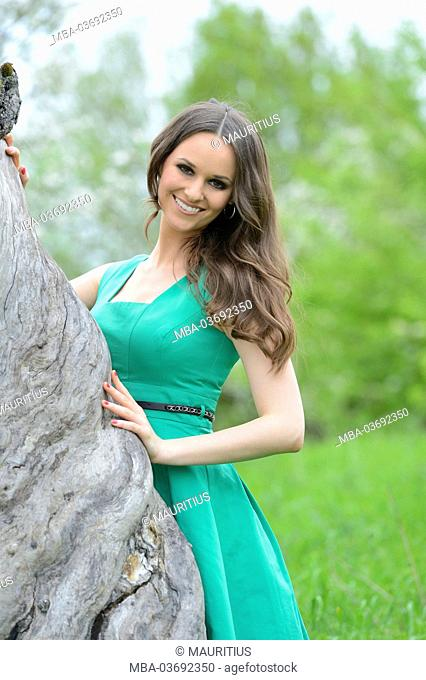 Young woman is standing beside an old trunk, looking into camera, looking into camera
