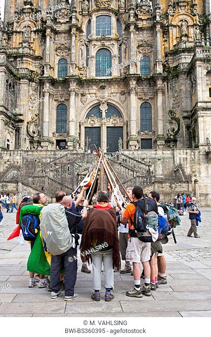Way of St. James, brasilian pilgrims drawing their walkingssticks together in front of the cathedral, Spain, Galicia, A Coruna, Santiago De Compostela