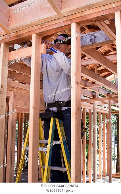 Mexican-American carpenter measuring and marking a piece of wood while working on a residential construction job