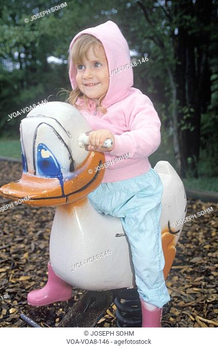 A preschool girl sitting on a duck ride