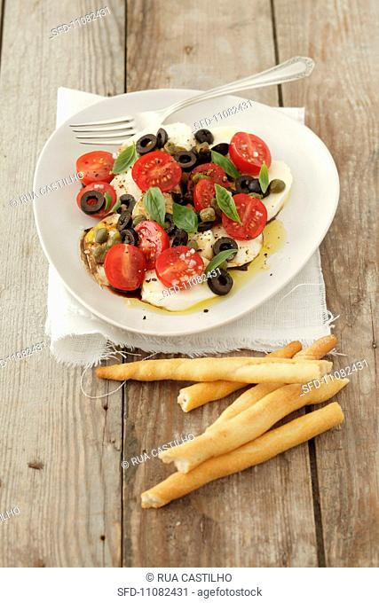 Cherry tomatoes with mozzarella, olives, capers and basil