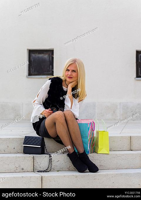 Attractive shopper woman with her shopping bags looking at camera