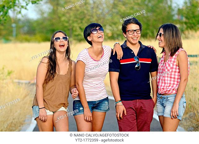 Group of three young women and a man have fun outdoors
