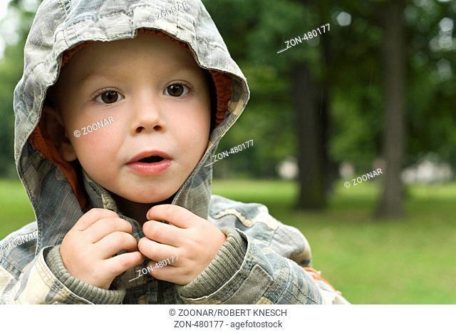 Vierjähriger Junge steht im Regen und macht die Kapuze seiner Jacke zu