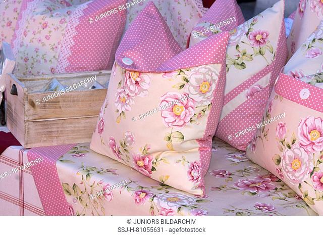 Homemade cushions offered in a market stall on the farmer`s market in Anger, Bavaria