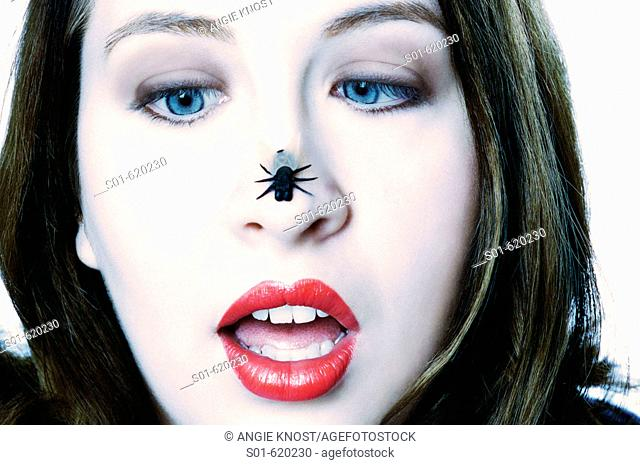This stock photo shows an attractive young woman, age 20-25, looking with crossed blue eyes at a plastic fly on her nose