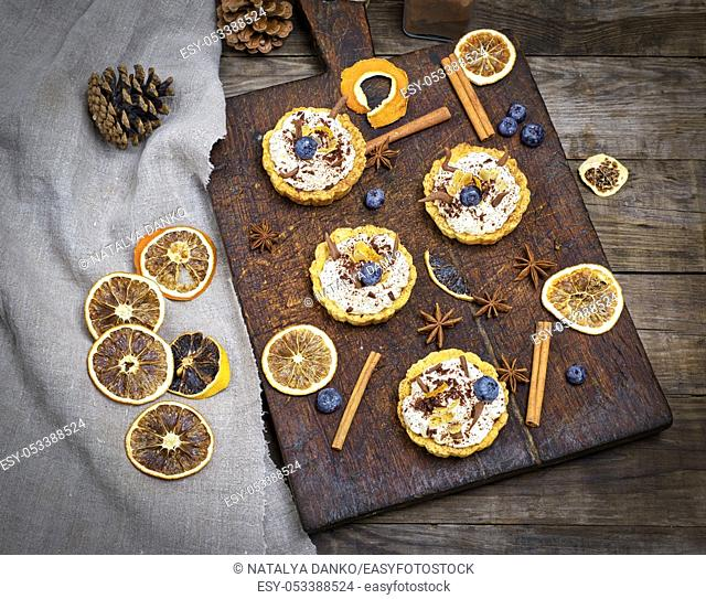 sweet cakes with white cream and chocolate powder on a brown wooden board, top view