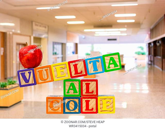 Vuelta al Cole translates to Back to School in spanish with wooden blocks with red apple on top. Background is a school entrance or corridor