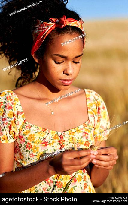 Young woman holding wheat crop in agricultural field during sunny day