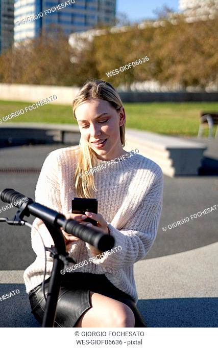 Portrait of young woman with kick scooter sitting on bench at sunlight using smartphone