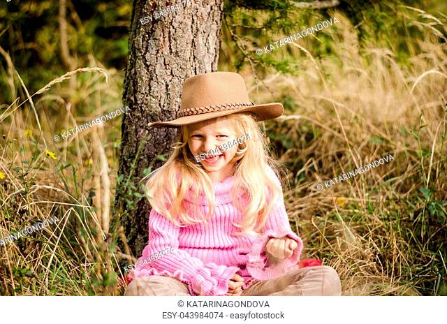 little lovely girl with long blond hair relaxing in autumn forest
