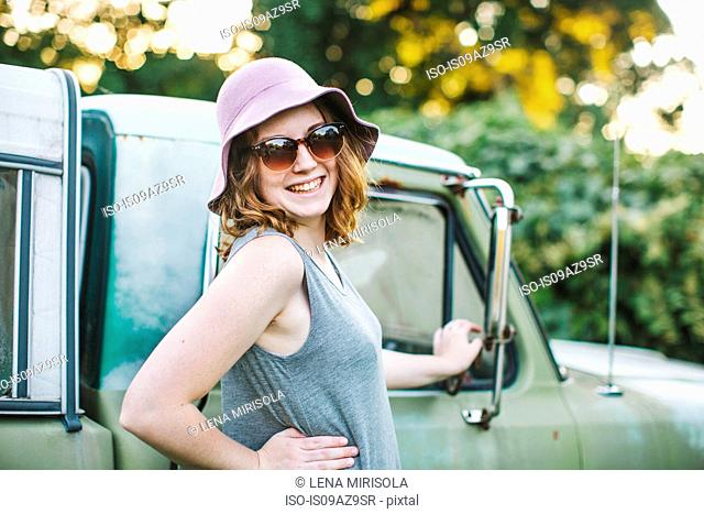 Woman wearing sunhat and sunglasses looking over shoulder at camera smiling