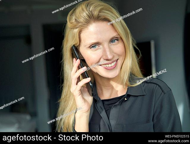 Portrait of smiling blond woman on the phone