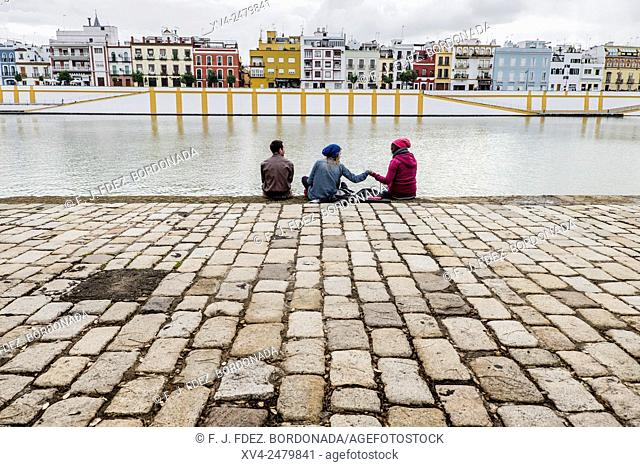 People group standing in riverside in front of Triana district. Seville, Andalusia, Spain