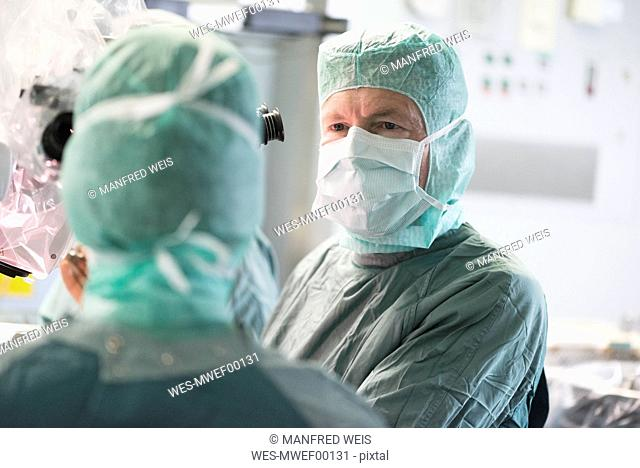 Neurosurgeon consulting colleague during an operation