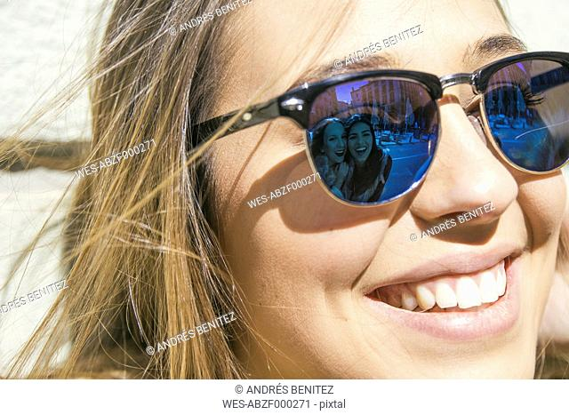 Friends of young woman reflecting at her sunglasses