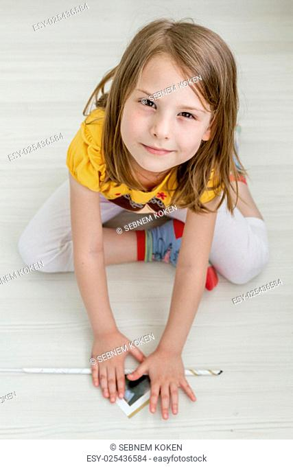 Little girl working on creative diy project from waste magazine