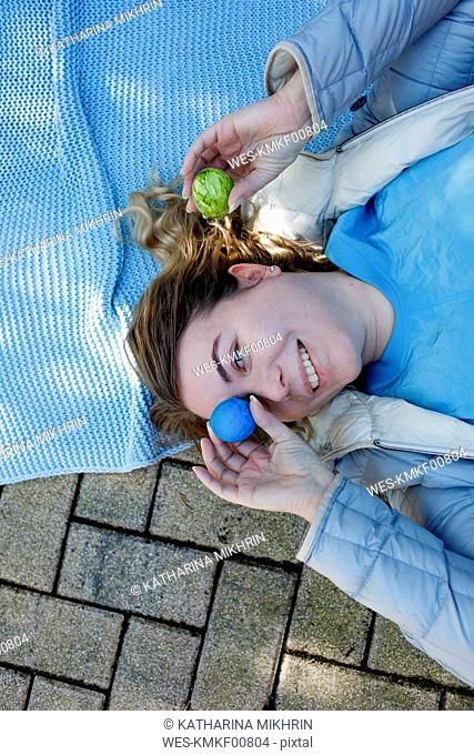 Woman lying on ground , covering eye with Easter egg