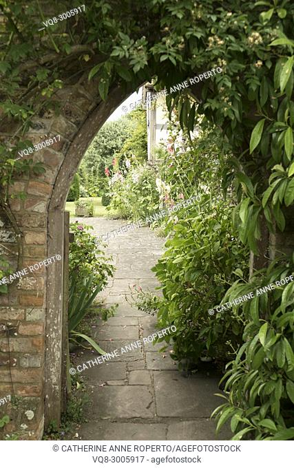 Arched doorway leading to the enchanted gardens of a medieval house in Frampton on Severn, the Cotswolds, England