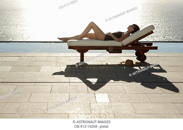Woman sunbathing in lounge chair at poolside overlooking ocean