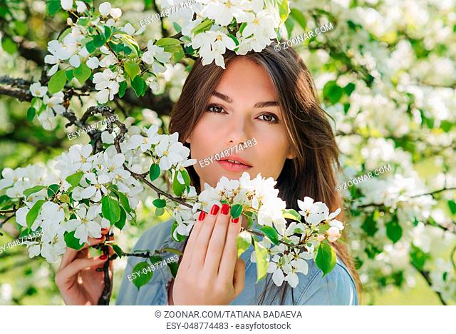 Beautiful young brunette woman standing near blooming apple tree
