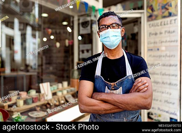 Male potter wearing mask with arms crossed standing outside ceramic shop