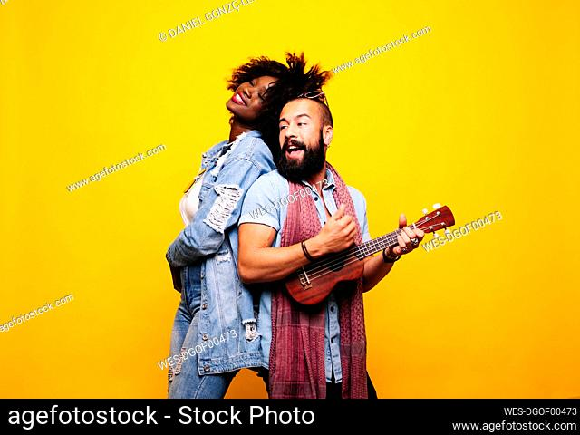 Happy young man with woman in studio playing ukulele