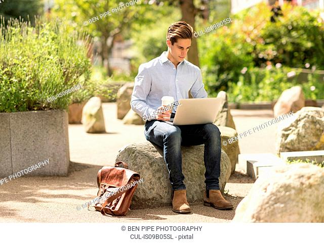 Young businessman reading laptop in city park