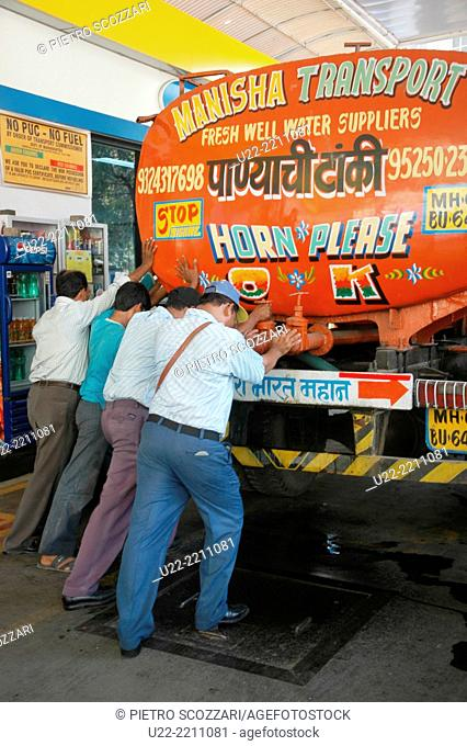 Mumbai, India: men pushing a truck without fuel to a gas station