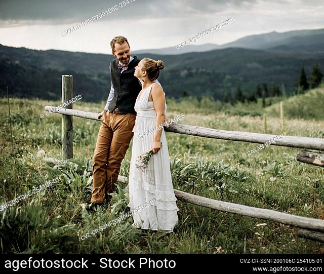 Newlyweds look at each other and smile while leaning on fence, Wyoming