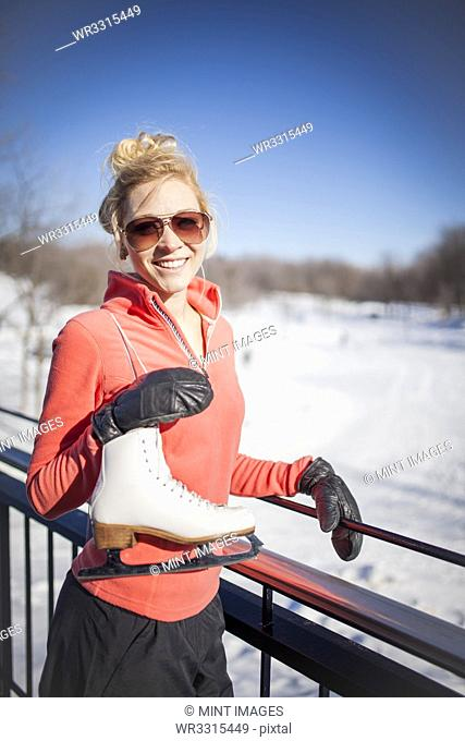 Caucasian woman carrying ice skates in winter