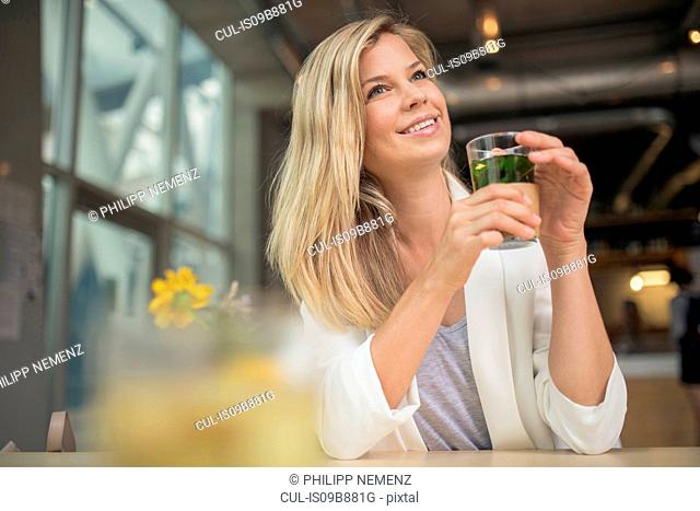 Portrait of woman in cafe holding drink looking away smiling